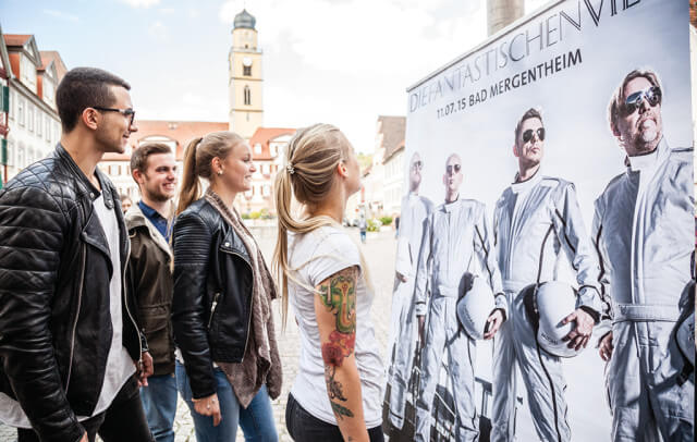 Studierende schauen sich Poster mit den Fantastischen Vier in Bad Mergenteim an