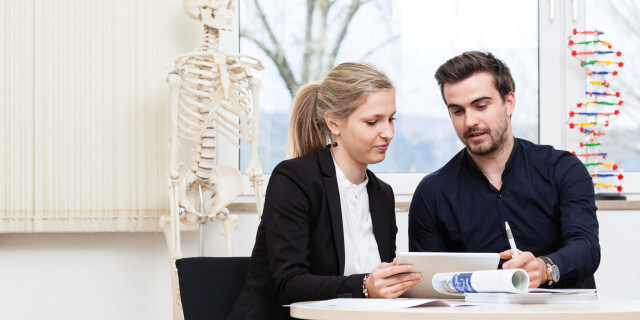 Studierende im Gesundheitsmanagement schauen in Tablet