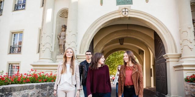 Studierende am Campus Bad Mergentheim laufen durch Schlosstor
