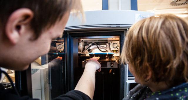 Studierende werfen Blick in eine Maschine